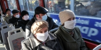 People wear protective masks as they ride the tram in the western Ukrainian city of Lviv on November 3, 2009. The Ukrainian health ministry raised on November 2 the death toll from the flu and respiratory problems to 67 on November 2, without detailing when the deaths took place or explaining the jump in the toll. AFP PHOTO/YURIY DYACHYSHYN - Городская Газета
