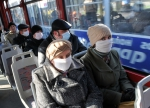People wear protective masks as they ride the tram in the western Ukrainian city of Lviv on November 3, 2009. The Ukrainian health ministry raised on November 2 the death toll from the flu and respiratory problems to 67 on November 2, without detailing when the deaths took place or explaining the jump in the toll. AFP PHOTO/YURIY DYACHYSHYN - http://orel-gazeta.ru/
